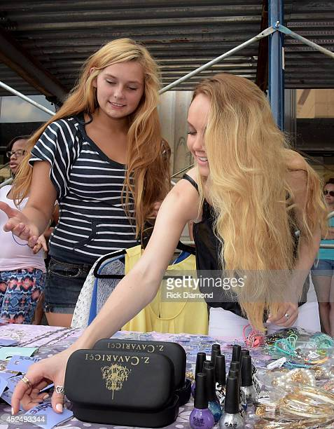 Season 4 winner of The Voice Danielle Bradbery helps a teen in the style studio at the Threads For Teens Mobile Boutique Tour at Hotel Indigo...