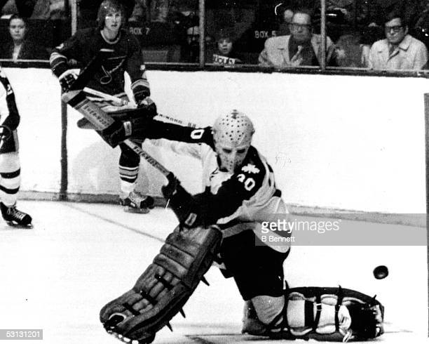 Bernie Parent looks back to see the puck get past him but bounce wide 122971