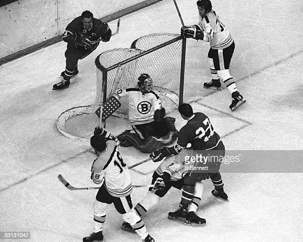 Bobby Orr defends against Frank Mahovlich in front of Gerry Cheevers as Jean Beliveau looks on.