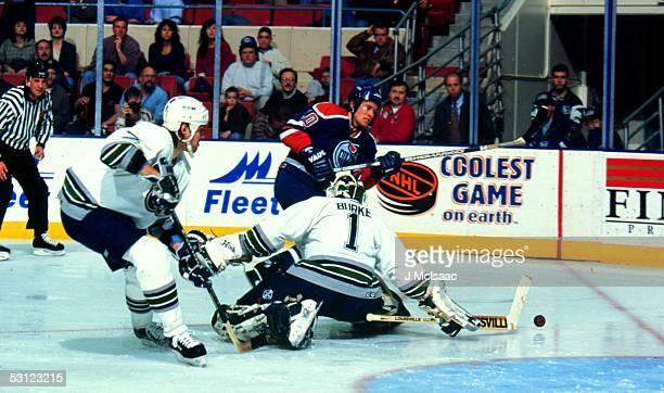 Edmonton's Mariusz Czerkawski slips the puck past Hartford goaltender Sean Burke
