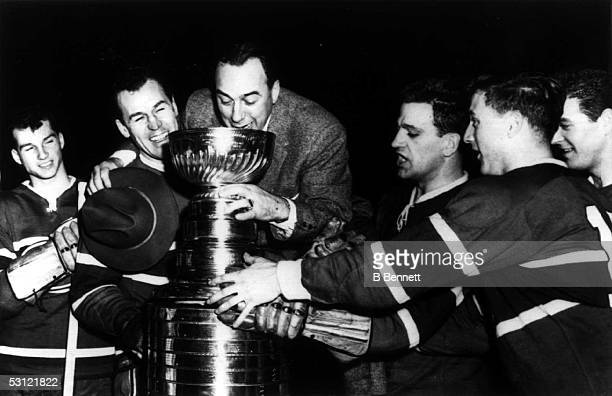 First year Montreal Canadiens coach Toe Blake drinks from the Stanley Cup with Don Marshall Captain Butch Bouchard Bernie Geoffrion Dickie Moore and...