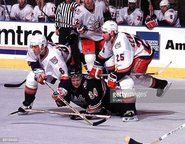 Jaroslav Svejkovsky of the Capitals is taken down by Mathieu Schneider and Manny Malhotra of the Rangers