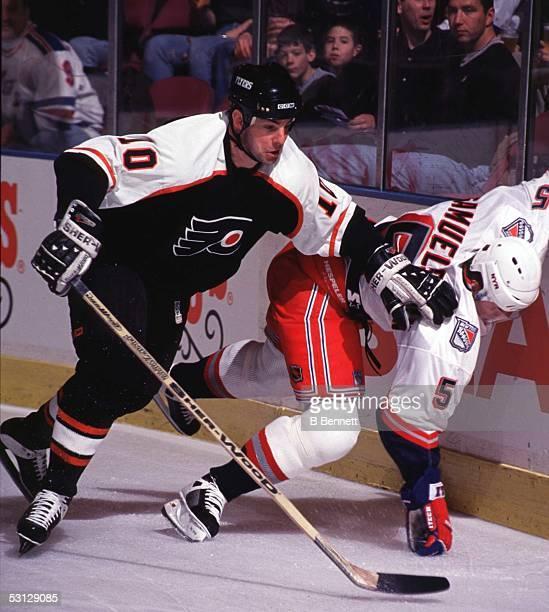 John Leclair of the Flyers battles Ulf Samuelsson of the Rangers