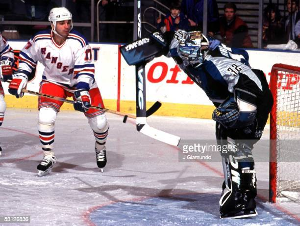 Kelly Hrudey knocks puck away from Kevin Stevens