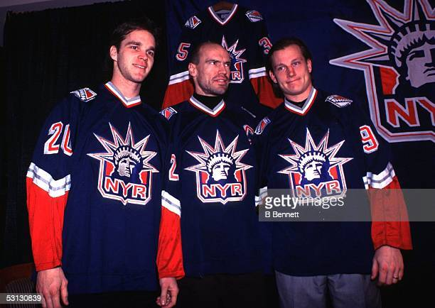 Luc Robitaille, Mark Messier and Adam Graves show the media the Rangers' third jersey for the first time during NY press conference.