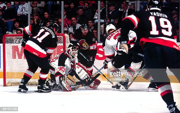 New Jersey goaltender Martin Brodeur holds the fort as defenseman Ken Daneyko tries to prevent Ottawa's Alexandre Daigle and Daniel Alfredsson from...