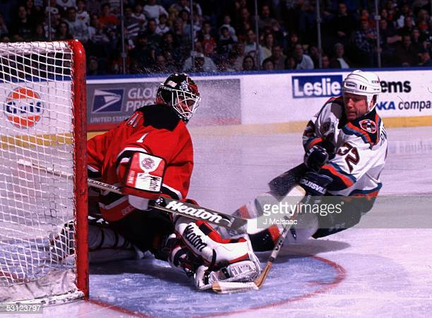 New Jersey goaltender Mike Dunham gets a pad on scoring attempt by New York Islander Niklas Andersson.