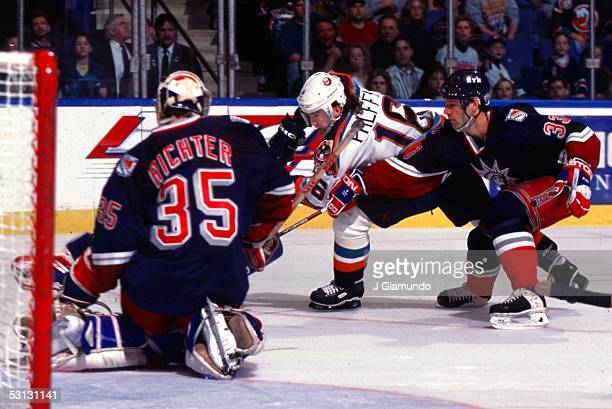 New York Islander Zigmund Palffy is hounded by Bruce Driver of the New York Rangers on a shot against goaltender Mike Richter