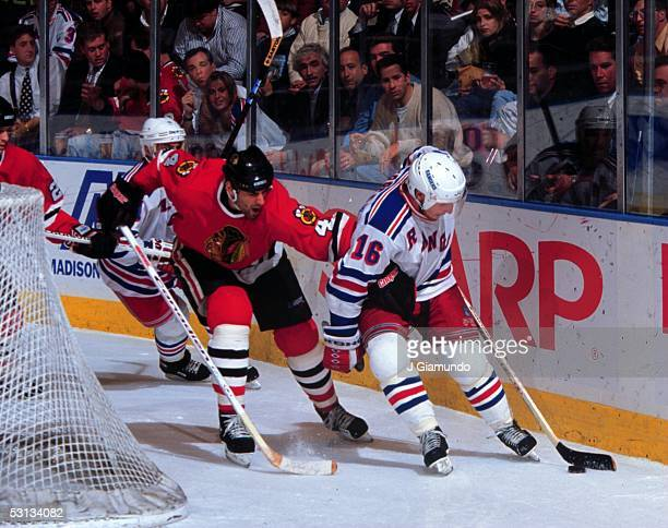Pat Verbeek grabs the puck behind the net with Keith Carney in hot pursuit