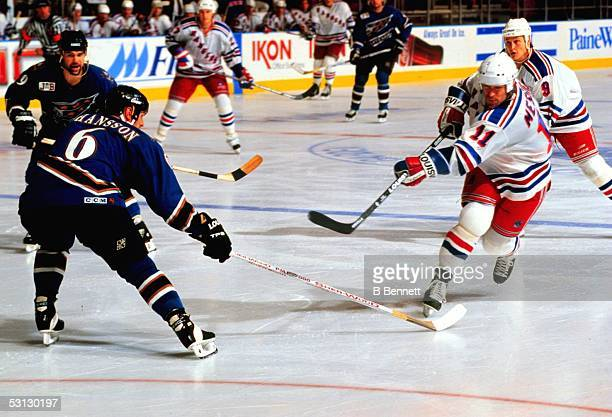 Ranger captain Mark Messier takes a shot as washington defenseman Calle Johansson tries to block the attempt