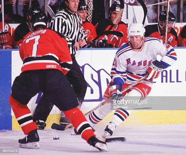 Scott Frasier of the Rangers tries to stickhandle around Devil's Defenseman Vlastimil Kroupa