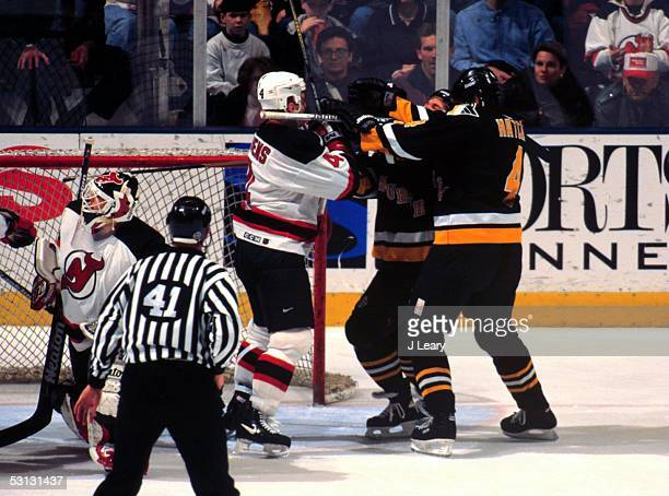 Scott Stevens Kevin Hatcher and unknown Penguin blast each other in front of NJ goaltender Martin Brodeur