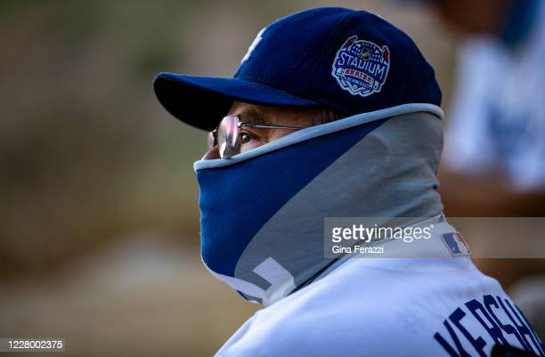 Season ticket holder David Baltazar of Long Beach wears a Dodgers neck gaiter as he sits with other fans watching the Dodgers play the San Francisco...