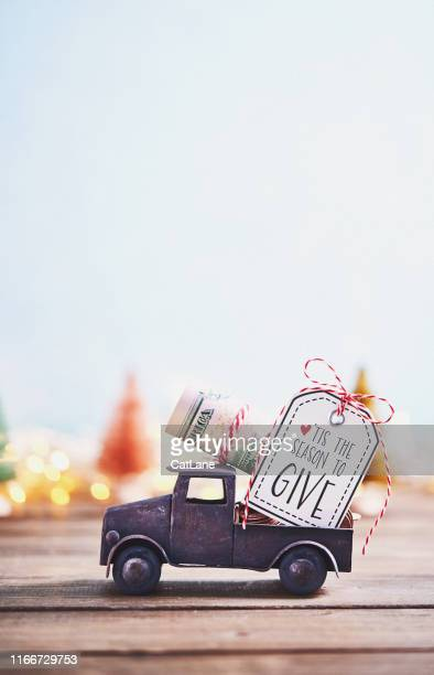 season to give. truck carrying roll of dollars with holiday background - christmas cash stock pictures, royalty-free photos & images