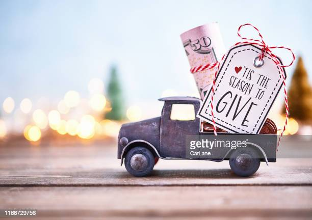 season to give. truck carrying roll of dollars with holiday background - donation box stock pictures, royalty-free photos & images