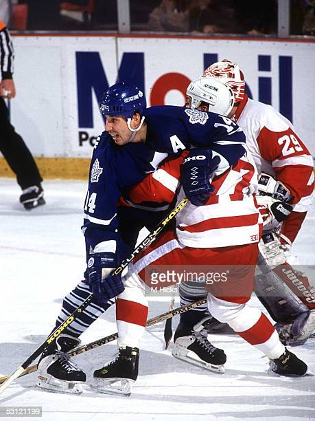 Toronto's Dave Andreychuk wrestles with Detroit's Paul Coffey in front of the net