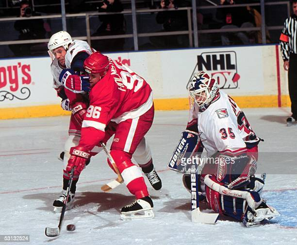 Ulf Samuelsson and Tomas Holmstrom battle for pucl in front of Mike Richter