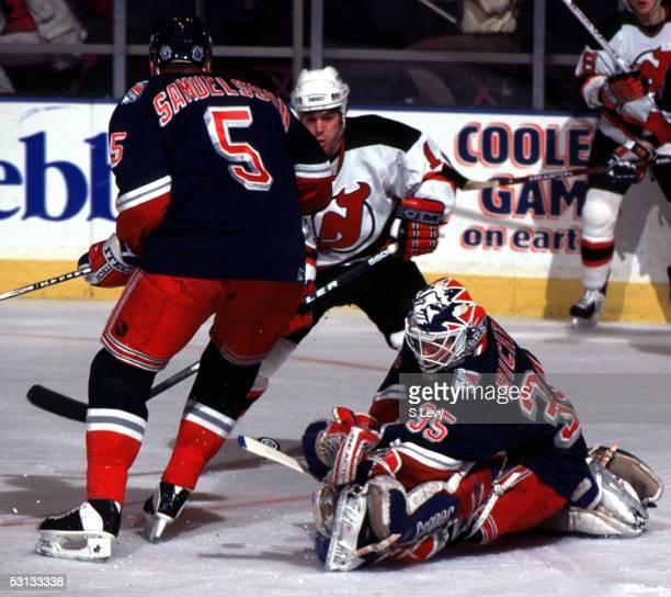 Ulf Samuelsson of the New York Rangers tries to keep New Jersey Devil Steve Sullivan away from goaltender Mike Richter