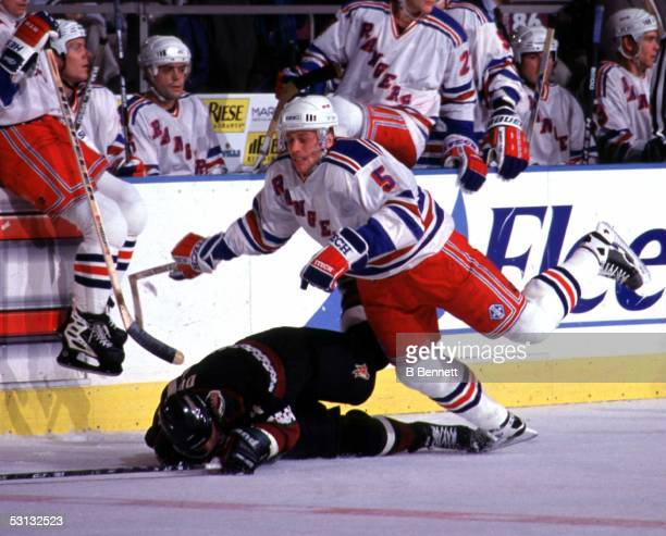Ulf Samuelsson trips over a fallen Gerald Diduck of the Phoenix Coyotes