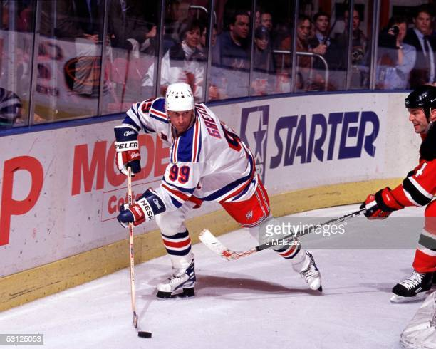 Wayne Gretzky works from his familiar spot behind the net as New Jersey's Scott Stevens gives chase