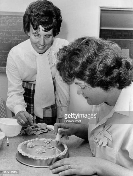Seasonal Cake Decorations Learned Mrs Donna Hanrahan instructor for Arvada YW Wives gives advice to Mrs James Byers as she practices decorating pan...