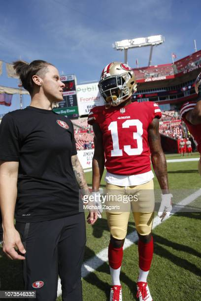 Seasonal Offensive Assistant Coach Katie Sowers and Richie James Jr #13 of the San Francisco 49ers talk on the field prior to the game against the...