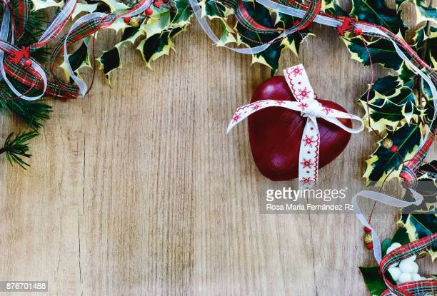 Seasonal rustic Christmas border composed holly leaves,  heart shape with a Christmas bow over a wooden background with copyspace, top view.