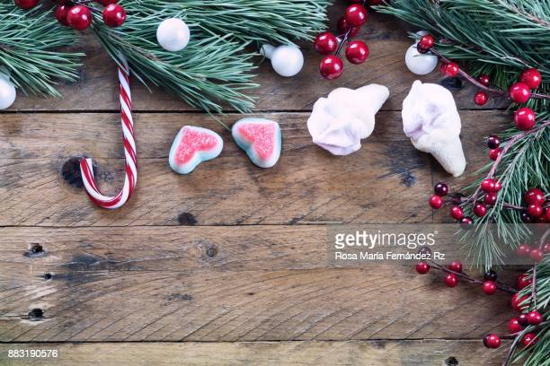 Seasonal rustic Christmas border composed of candy canes and marshmallow,  fir tree branches and mistletoe seed on vintage wooden background. Top view and copy space