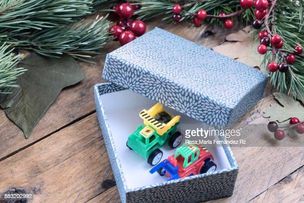 seasonal rustic christmas border composed of open gift box with toys inside,  fir tree branches and mistletoe seed on rustic wooden background. directly above. selective focus - toy box stock pictures, royalty-free photos & images