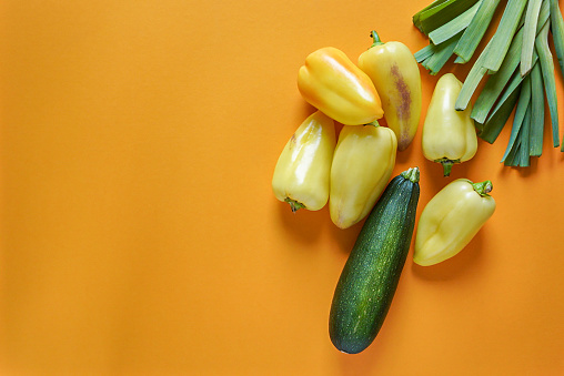 seasonal vegetables of orange, green, yellow and purple colors lie freely on a yellow background 1168544716