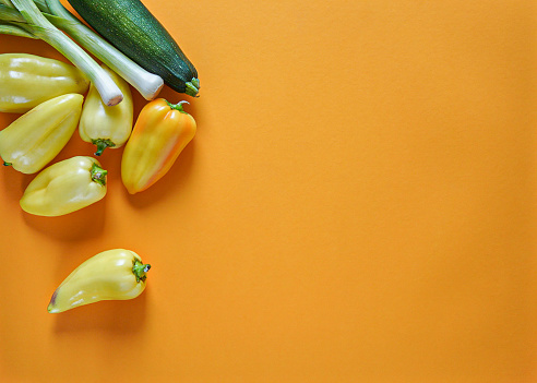 seasonal vegetables of orange, green, yellow and purple colors lie freely on a yellow background 1168544721