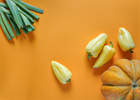 seasonal vegetables of orange, green, yellow and purple colors lie freely on a yellow background 1168544737