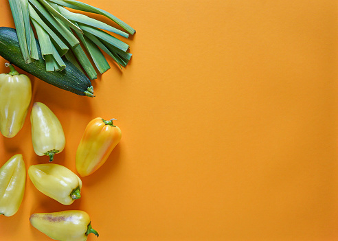 seasonal vegetables of orange, green, yellow and purple colors lie freely on a yellow background 1168544741
