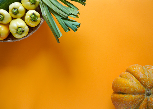seasonal vegetables of orange, green, yellow and purple colors lie freely on a yellow background 1168544744