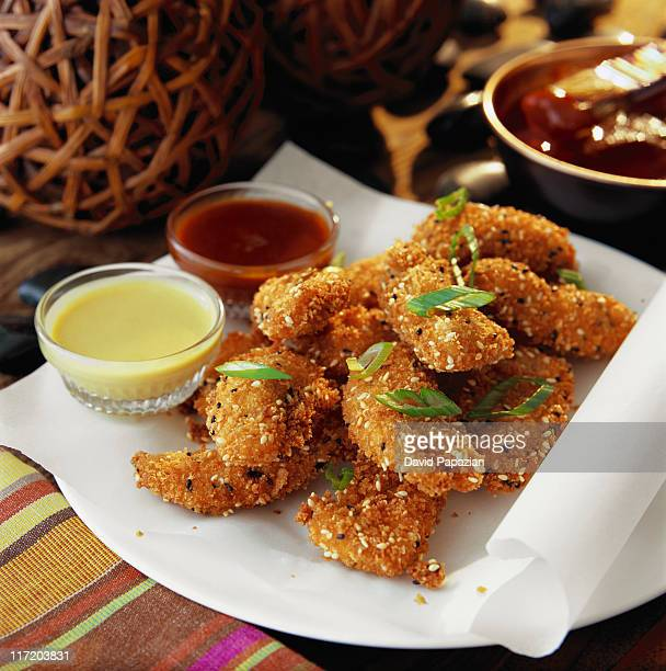 Seasoned chicken fingers with hot mustard and spicy barbecue sauce