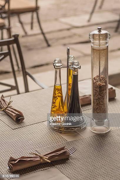 Seasoning bottles and napkins on table in restaurant