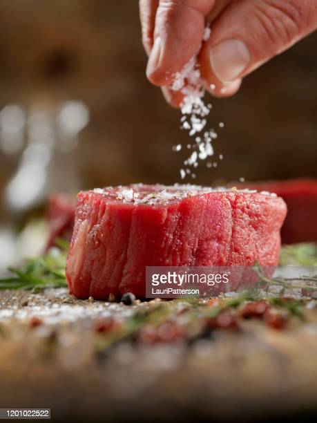 seasoning raw fillet mignon steaks - meat stock pictures, royalty-free photos & images