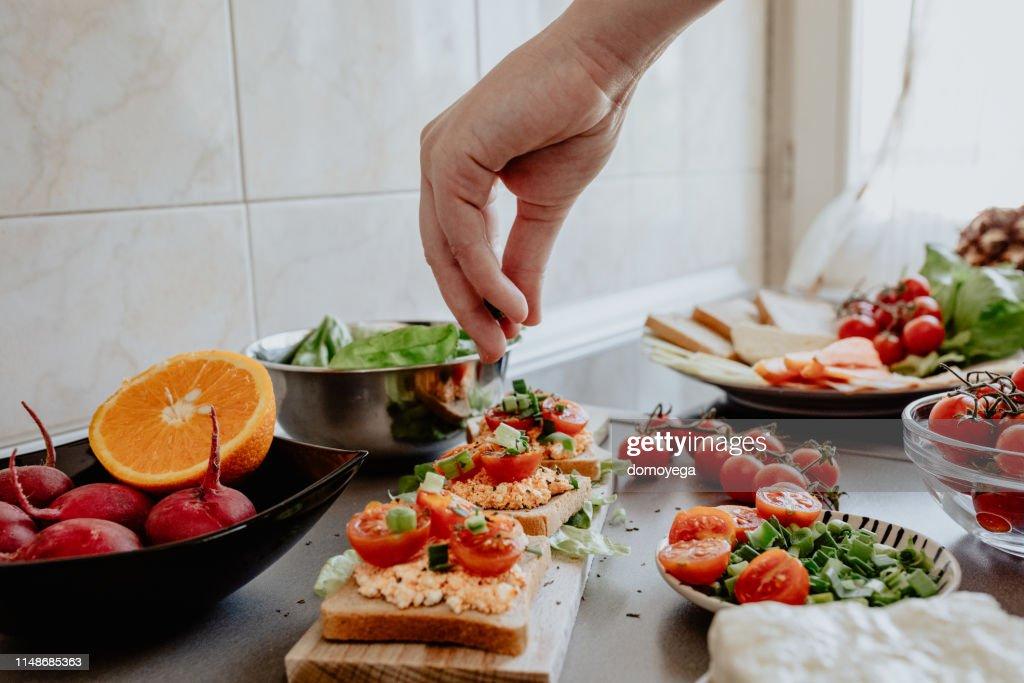 Seasoning tasty bruscheta in the kitchen : Stock Photo