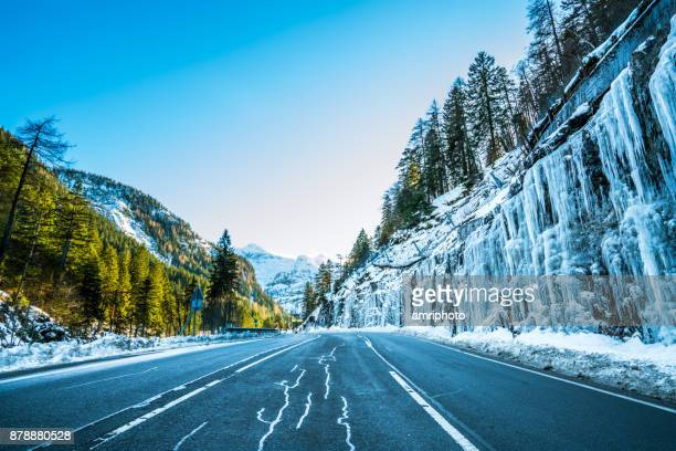4 seasons - early onset of winter, country road with icicles in mountains - january stock pictures, royalty-free photos & images