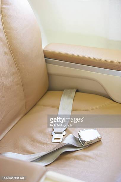 Seat belt across empty seat on airplane, elevated view