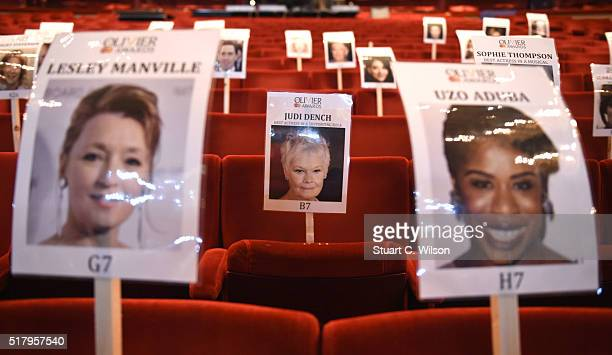 Seat markers with faces of nominees are seen in position during the 'heads on sticks' photocall ahead of the Olivier Awards which takes place on...