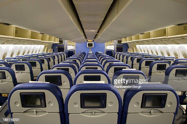 Seat rows with video screens inside an airplane