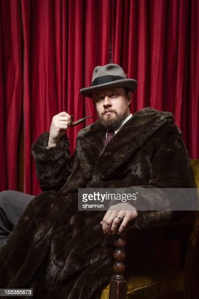Seated Bearded Man Wearing Fedora, Fur Coat, Holding Pipe