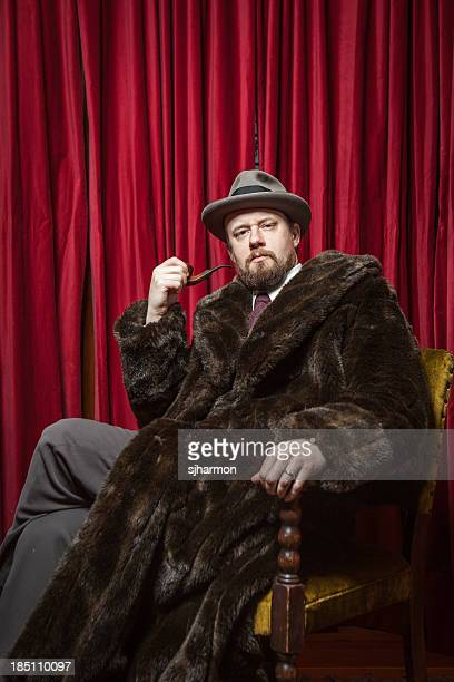 Seated Bearded Man Wearing Fedora, Fur Coat, Holding Pipe