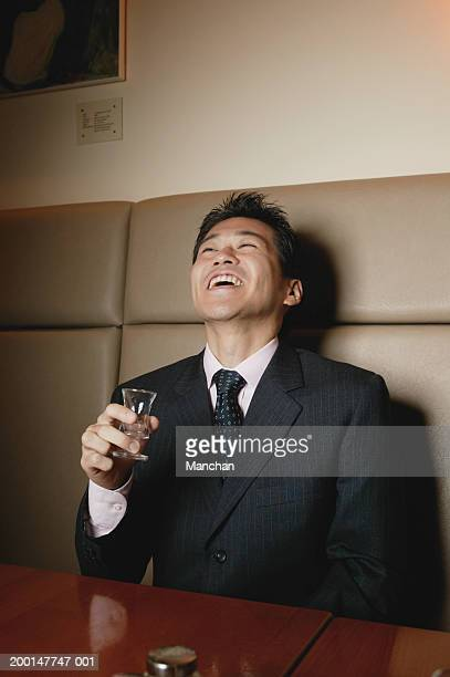 Seated businessman holding shot glass, laughing