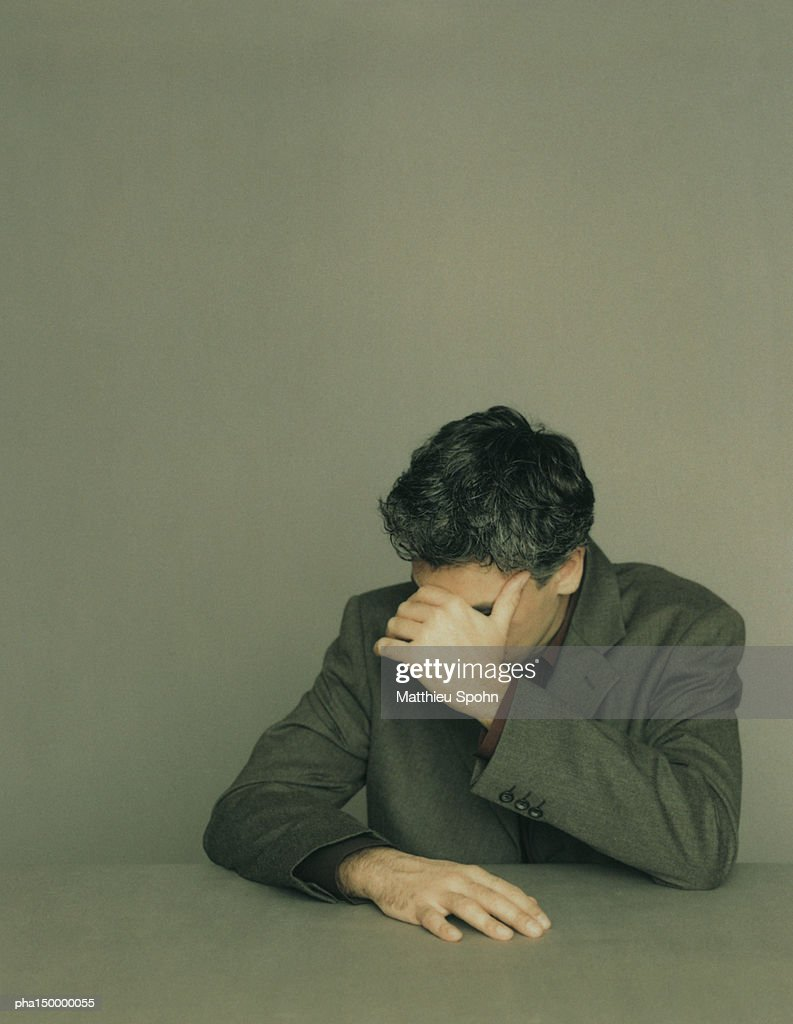 Seated businessman looking down with hand covering eyes, portrait : Stockfoto