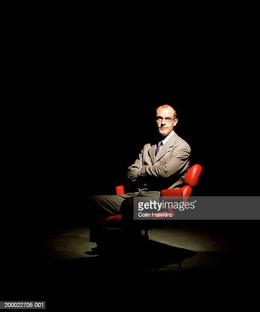 Seated businessman under spotlight, portrait