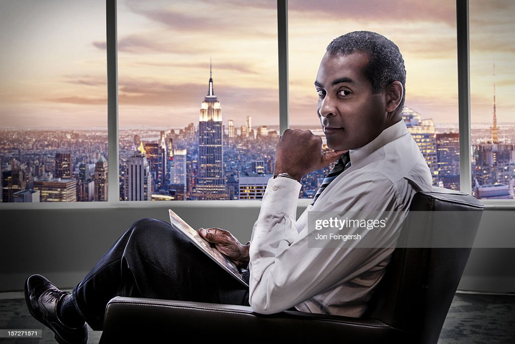Seated Businessman with cityscape behind. : Stock Photo