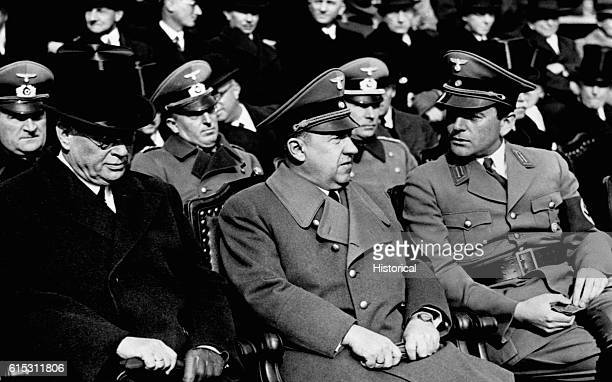Seated in the audience at a rally or speech are left to right Nazi state secretary Remhardt Reich finance minister Walter Funk and state architect...