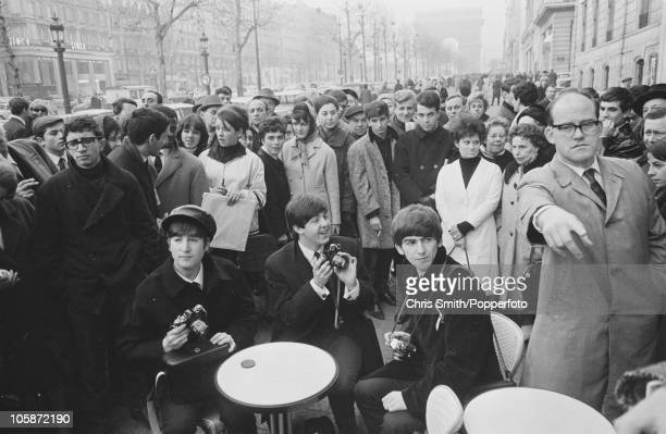John Lennon Paul McCartney and George Harrison of The Beatles draw a crowd at a cafe on the ChampsElysees Paris 1964 The group are performing at the...